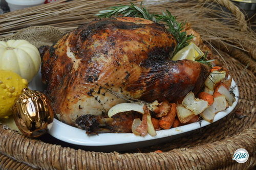 Whole Thanksgiving turkey brined and roasted.  Surrounded by roasted vegetables, rosemary, and citrus. Set against holiday backdrop.