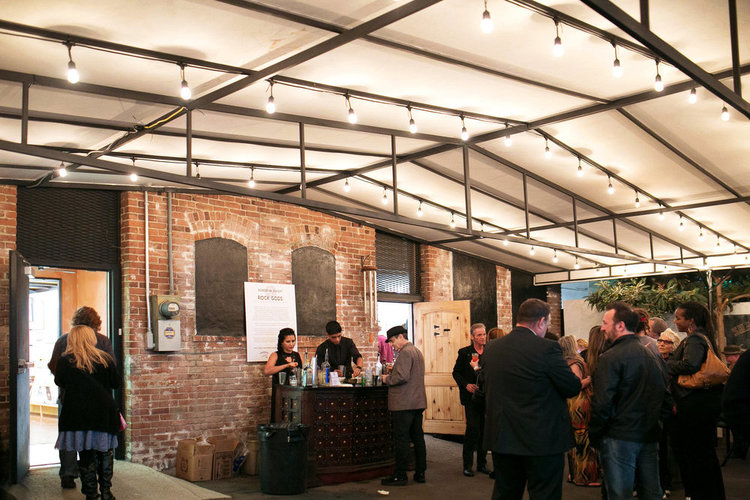 Crowd enjoying drinks outdoors under the covered patio at Mr Musichead