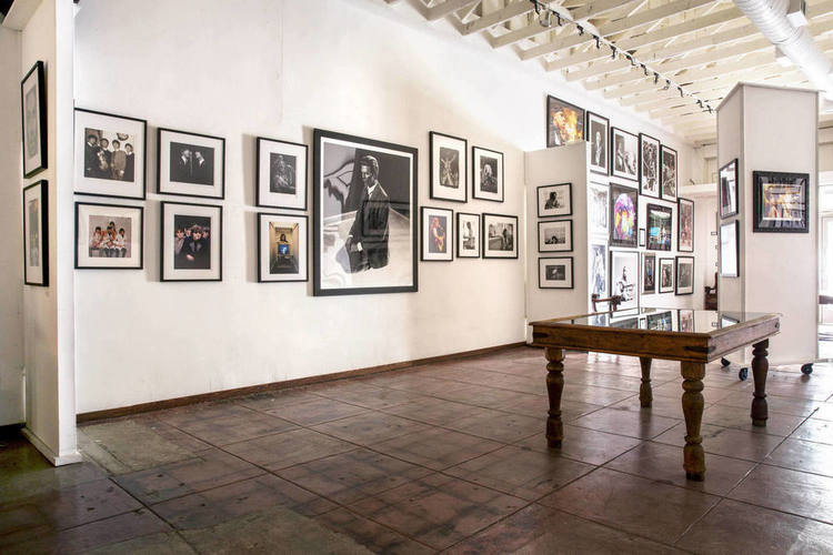 The large, light gallery space is covered with photos of important moments in music history.