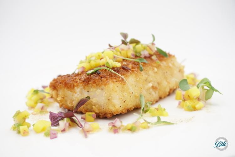 Closeup of wild Mahi Mahi with macadamia crust on white plate, topped by mango salsa, microgreens, rum beurre noisette
