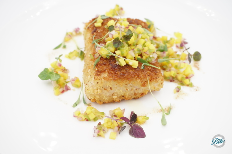 Wild Mahi Mahi with macadamia crust on white plate, topped by mango salsa, microgreens, rum beurre noisette.  Viewed from the top.