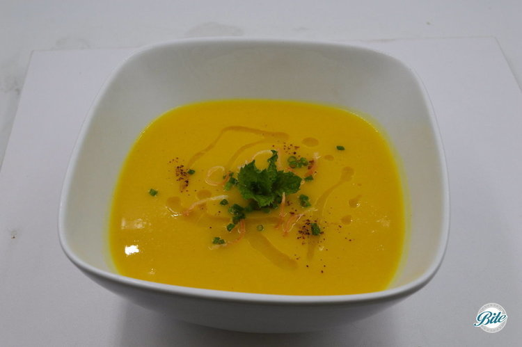 Butternut Squash soup with coconut milk, carrots, and spiced with ginger. In white bowl.