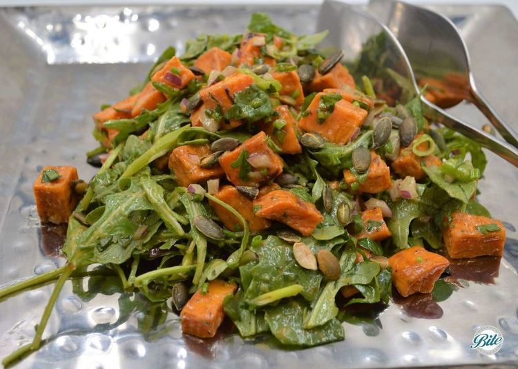 Roasted sweet potato, arugula, scallions, Italian parsley, toasted pumpkin seed, chives, red onion, cayenne, oregano, smoke paprika, red wine vin, maple, garlic & shallot dressing. On a steel platter with serving tongs.