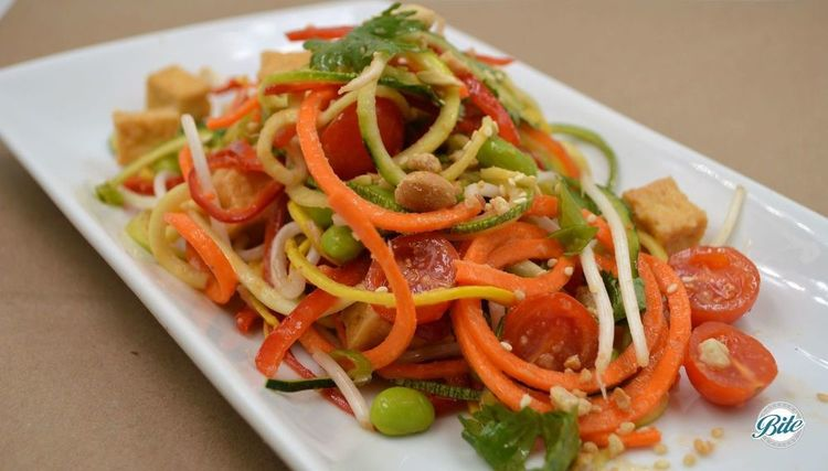 Spiraled zucchini & carrot, red pepper, red cabbage, edamame, green onion, sesame seed, Fresno chili, bean sprouts, cilantro, fried firm tofu w fermented tofu, garlic, almond, ginger, lime & sesame oil dressing. Served on a small plate.