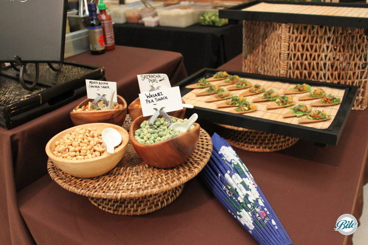 Mixed asian snacks in bowls on display next to lettuce wraps on spoons. Wasabi peas, sriracha peas, mixed asian crackers.