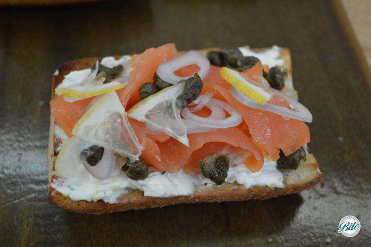 Tartine with smoked salmon, lemon-chive cream cheese, shallot, lemon and fried capers