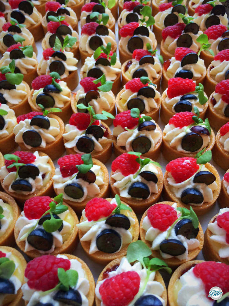 Lemon tarts on a tray with whipped cream, fresh raspberry and blueberry, and garnish