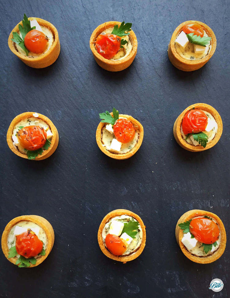 Herb Tarts with tomato and cheese on slate backdrop