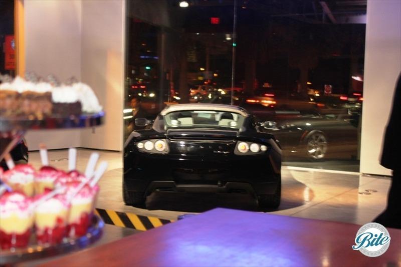 Investor meeting at Tesla showroom.  Dessert shot in foreground.