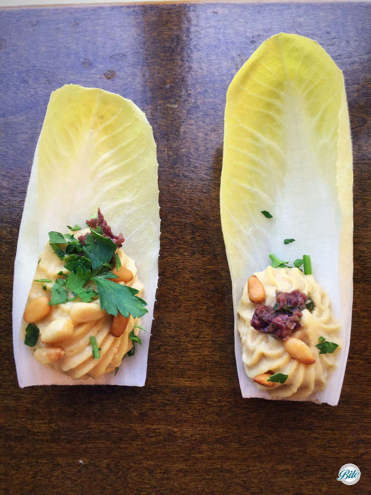 Belgian Endive Capape with Hummus and Pine Nuts on wooden serving tray
