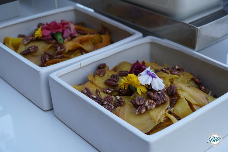 Shaved Gold Beets with toasted pecans and edible flowers. On Market Display in square serving bowls.