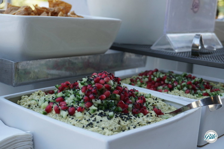 House made edamame hummus topped with cucumber, pomegranate, and sesame seeds. Served with pita chips in square bowls on market display