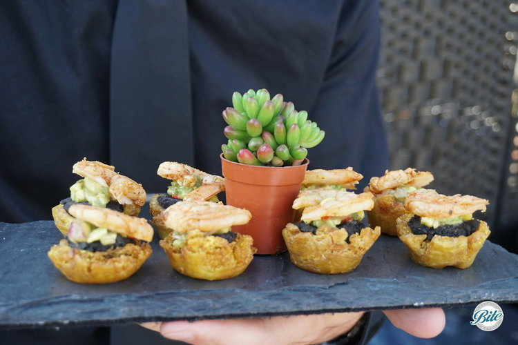 Tostone crispy  plantain cups, tequila lime shrimp, avocado-mango salsa, black  bean.  Passed on slate tray.