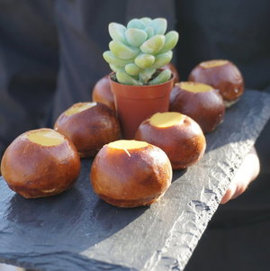 Pretzel canapes w/ cheese fondue and server in black