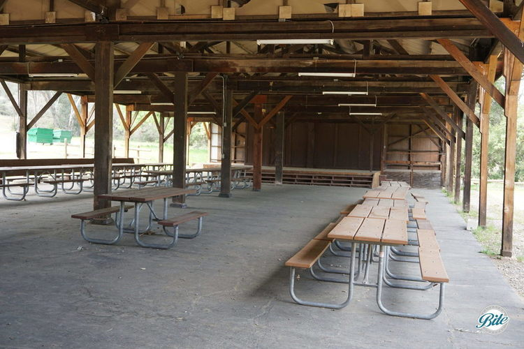 A large pavilion with tables provides both a stage and place perfect for a large group to eat, dance, or give speeches