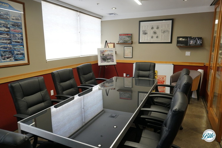 A long conference table surrounded by comfortable executive chairs in a private meeting space reflects the automotive spirit of its surroundings