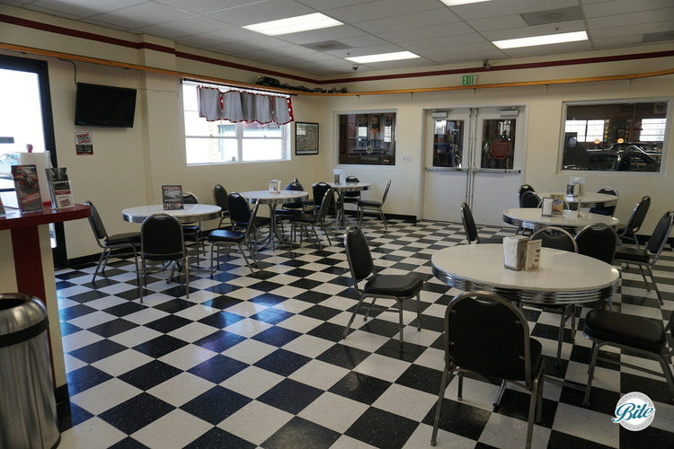 A black and white checkered floor with retro 50's tables in the ice cream parlor at the Automobile Driving Museum