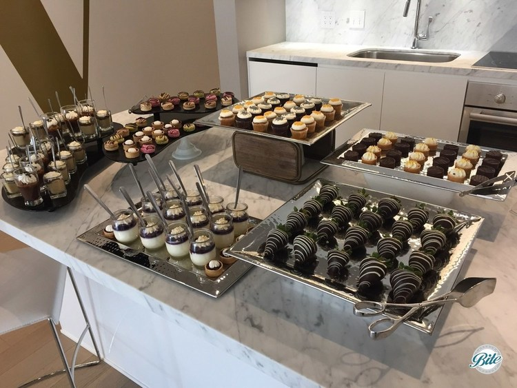 A modern dessert assortment displayed on a marble counter with risers.  Chocolate covered strawberries, dessert tarts, mini cupcakes, dessert shots, macaron