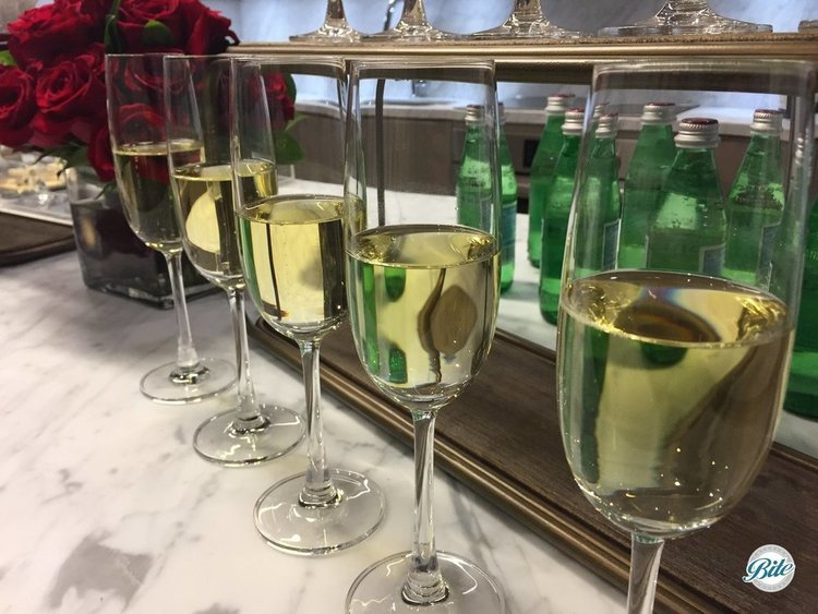 Champagne glasses lined up on display next to a vase filled with roses