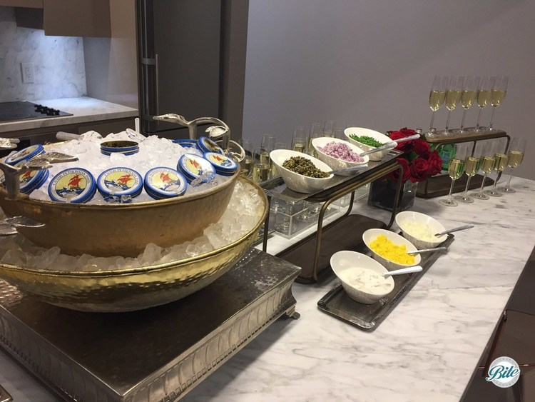 Caviar bar with bread and toppings laid out next to champagne for a small group tasting