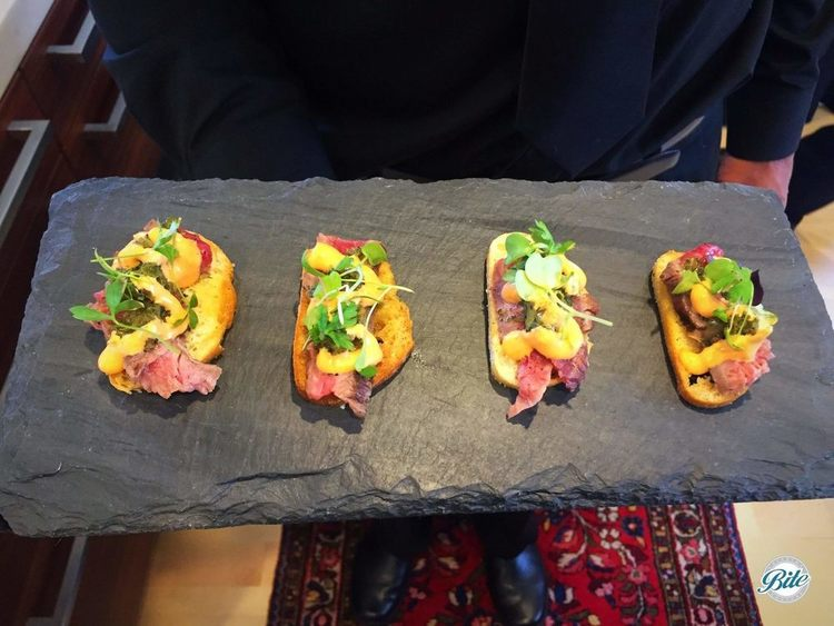 Grilled Flank Steak Crostini with chimichurri, grilled vidalia relish and sriracha aioli. Passed service on a slate tray