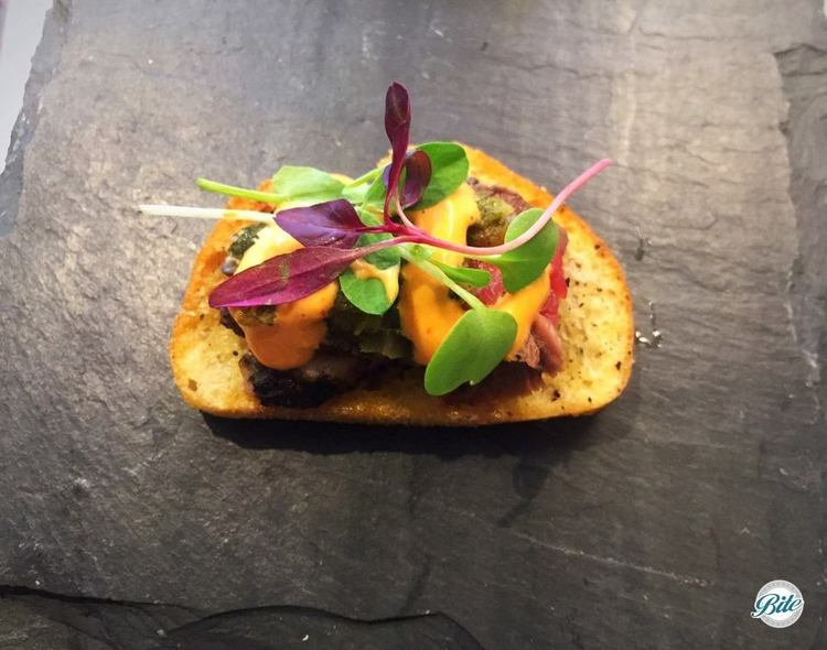Grilled flank steak crostini with chimichurri, grilled vidalia relish and sriracha aioli.  Closeup shot displayed on slate tray.