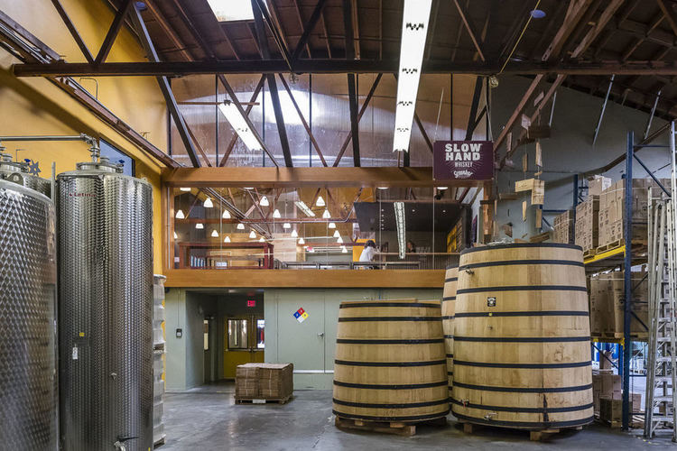 Large wooden vats on the distillery floor with a look into the Skybox tasting room