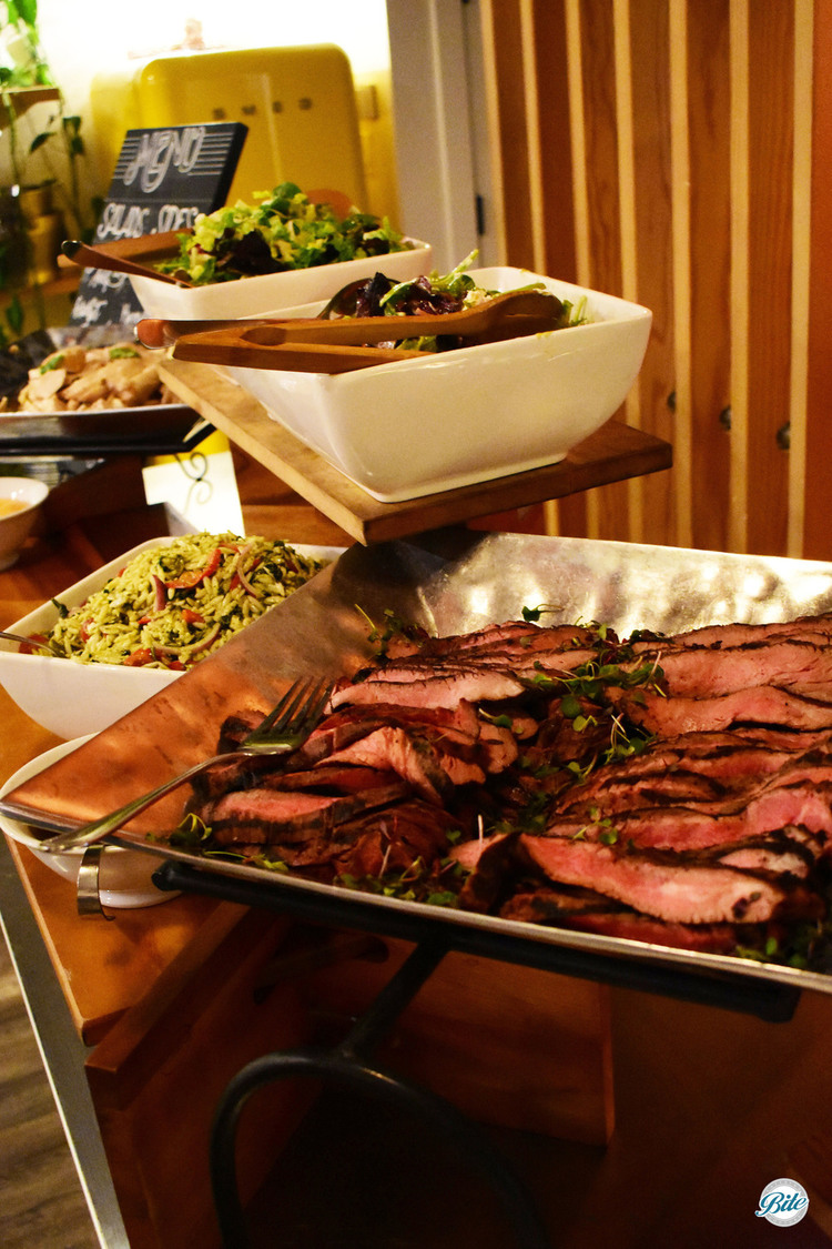Marinated flank steak elevated in metal display. Served with chimmichurri and sriracha aioli as part of a seasonal buffet