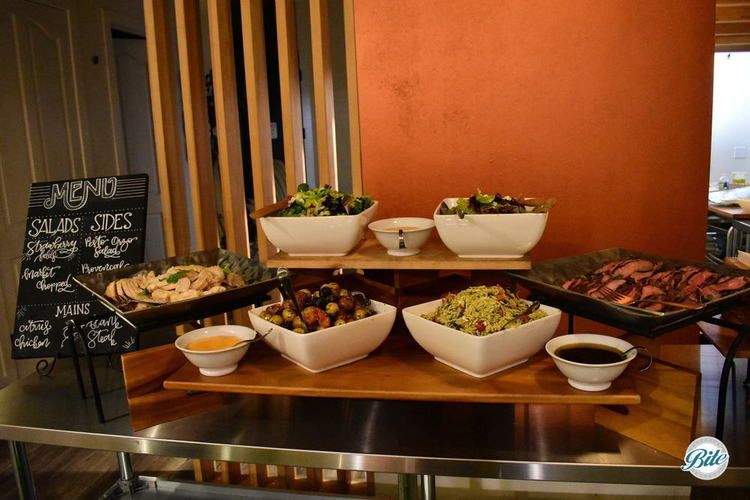 Seasonal buffet setup on table with a mix of salads, steak, chicken, fish, orzo, and potatoes