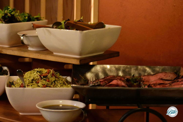 Closeup of a seasonal menu on a buffet. The orzo salad is piled high next to two other salads and slices of marinated flank steak.