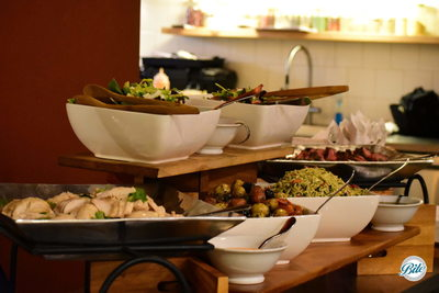 Bite loves buffets displayed on different levels! Visible are slices of a citrus chicken, multiple salads (Spanish Harvest and Strawberry Fields), a pesto orzo salad, provencal potatoes, flank steak