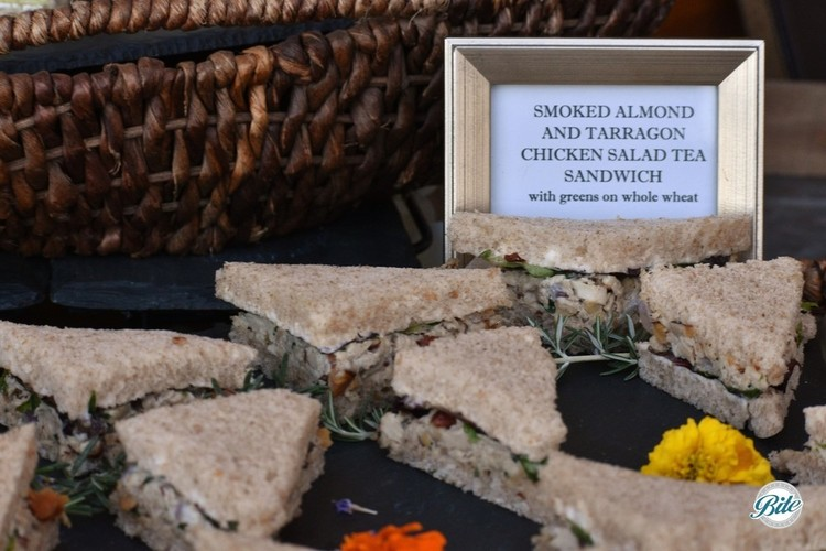 Smoked Almond and Tarragon Chicken Salad Tea Sandwich with greens on whole wheat.  In triangles on a slate tray