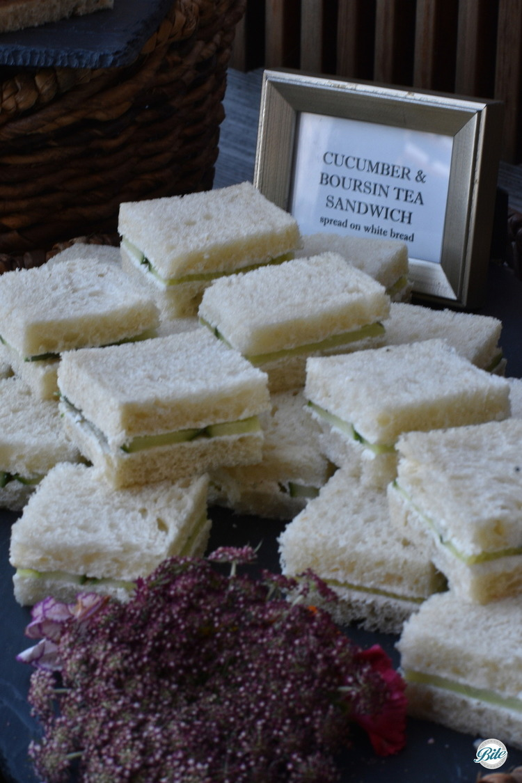 Cucumber and Boursin Tea Sandwiches on white bread.  Cut in squares and served on a slate tray presented in a basket