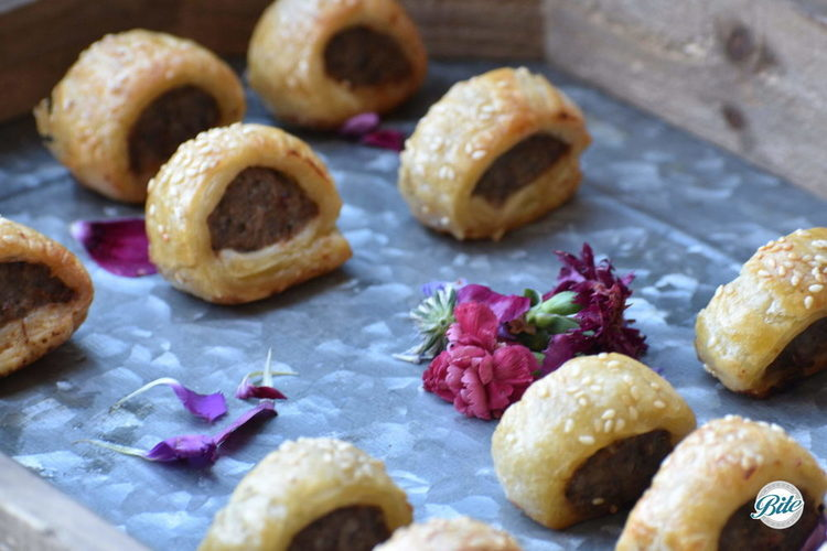 English Sausage Rolls with mustard dipping sauce passed on a wooden tray with flower garnish