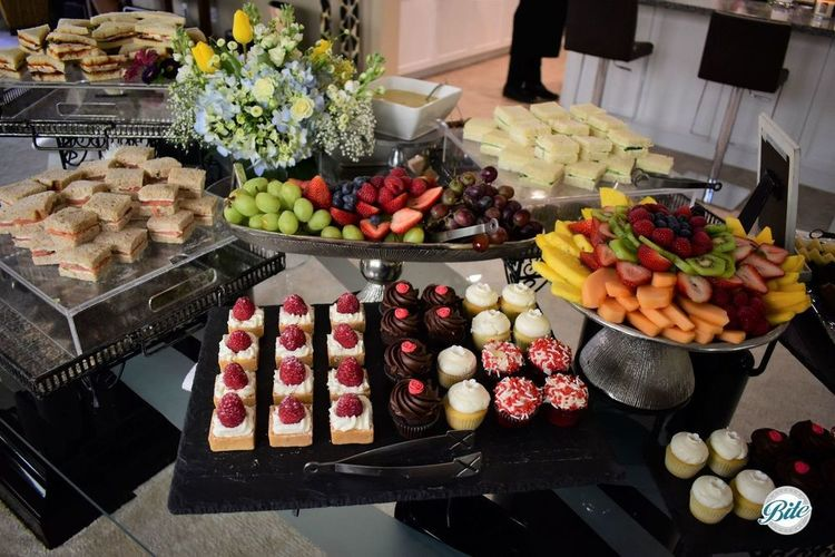 Dessert assorment with lemon bars and mini cupcakes next to fruit platters and tea sandwiches
