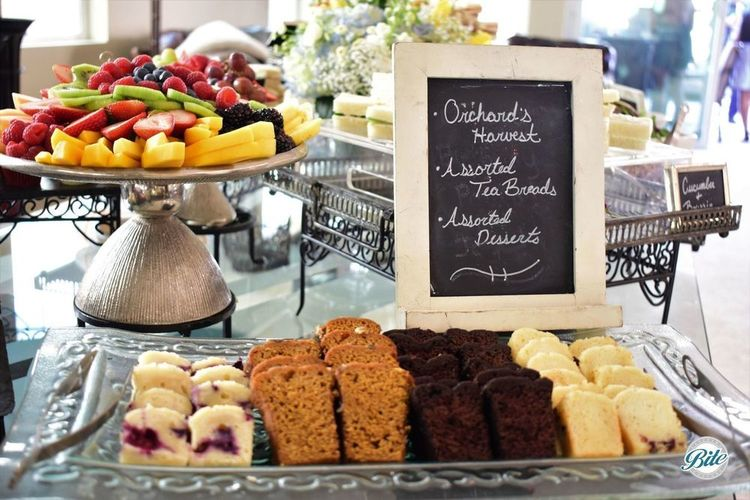 Assorted tea breads with orchard's harvest and tea sandwiches in the background