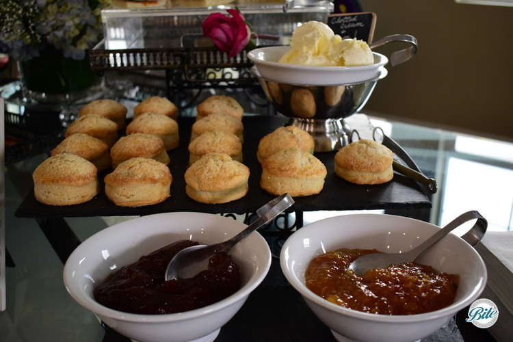 Fresh baked scones displayed on slate tray set out with clotted cream and two different types of jam in bowls