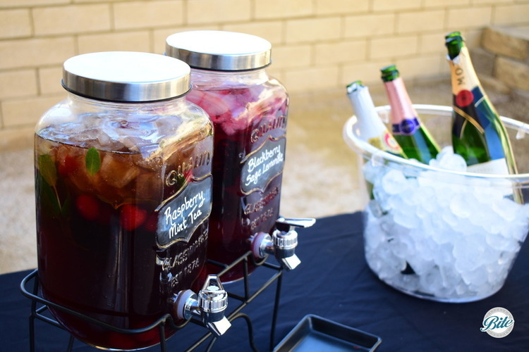 Drink station.  Raspberry mint tea and blueberry sage lemonade next to some bubbly.