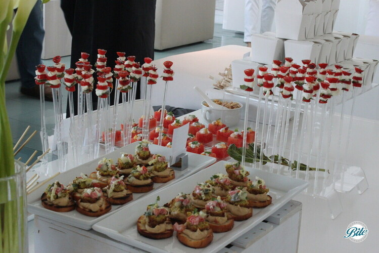 Table laden with crostini, caprese skewers, watermelon cubes - a perfect bite for summer
