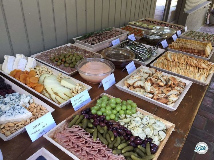 Selection of hearty platters on wooden table for buffet. Antipasto, cheese and charcuterie, flank steak crostini with sriracha aoili