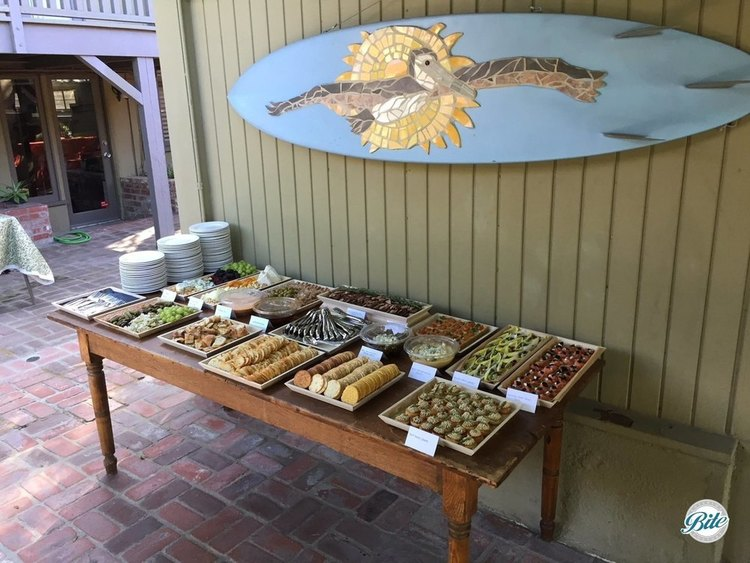 Appetizers laid out on buffet table outdoors under hanging surfboard. Wooden trays highlight selections from our delivery option with disposable trays.