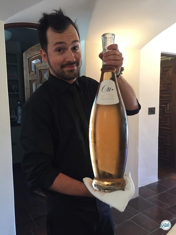 Bartender bringing out a magnum bottle of wine
