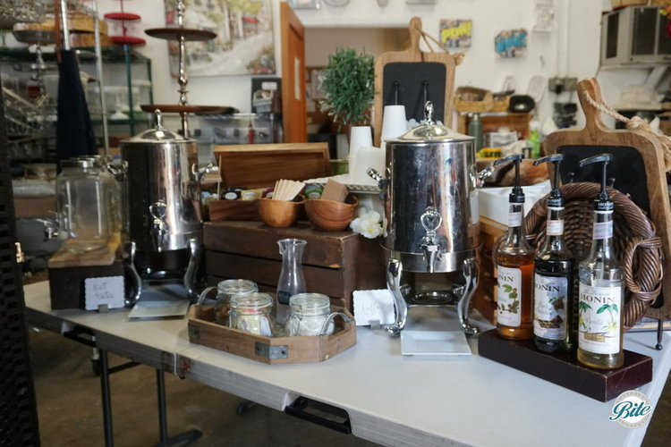 Coffee and hot water  in silver urns with syrups, stirrers, sugar for a small coffee bar in an office