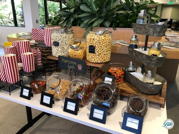 Popcorn bar with caramel, classic, and cheese popcorns and assorted seasonings. Displayed with assorted candies including peanuts, gummies, chocolate pretzels, chcocolate chips, and reese's pieces.