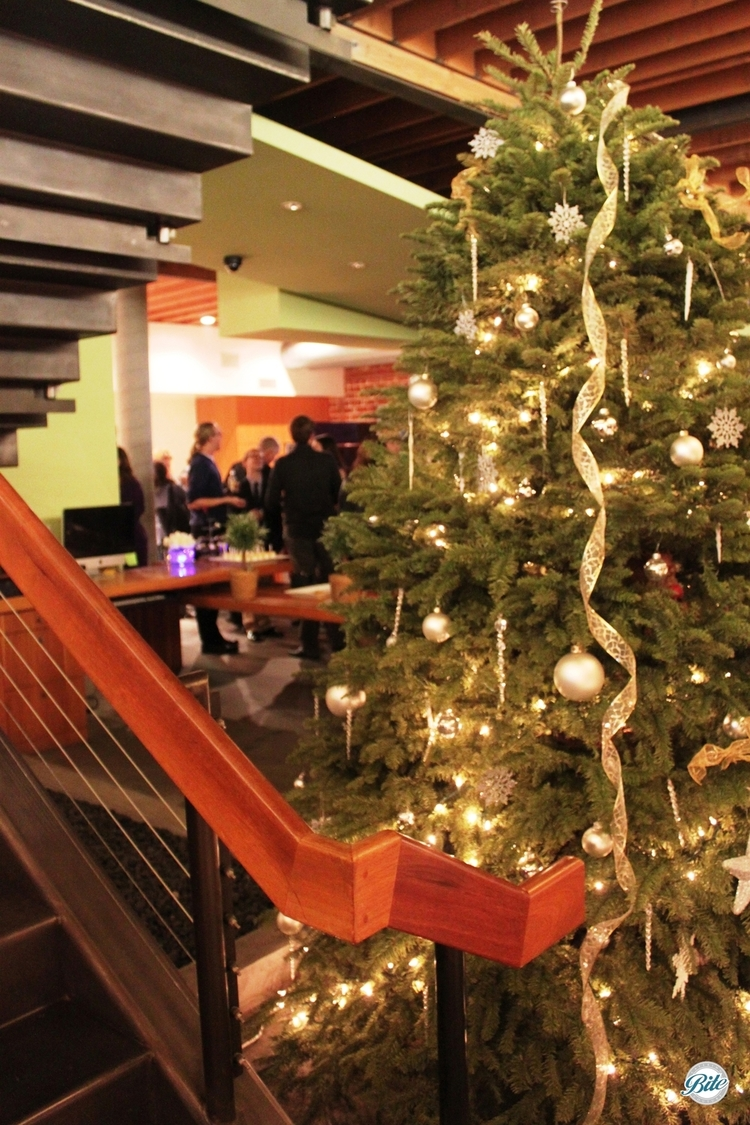 A Christmas tree under the stairs with holiday party in the background