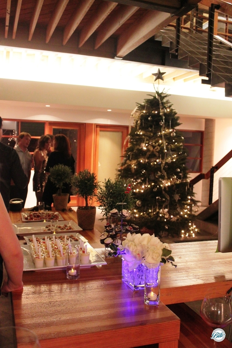 Setting out a dessert table at an office holiday party with christmas tree in the background