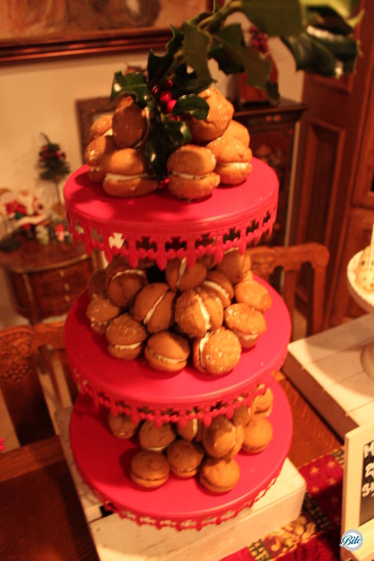 Gingerbread whoopie pies displayed on red riser with mistletoe