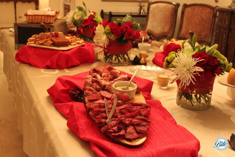 Charcuterie plate with assorted italian meats and spicy mustard on holiday cheese and charcuterie table.