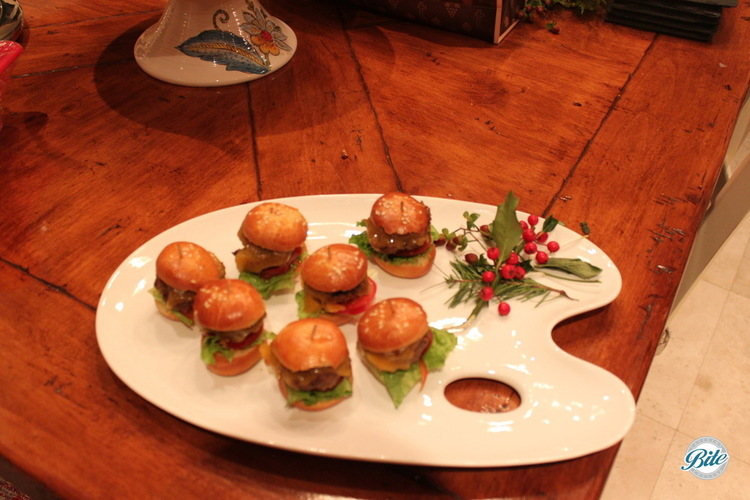 Miniature BBQ Western Sirloin Cheeseburgers Served On Homemade Brioche Buns.  Served on tray garnished with mistletoe