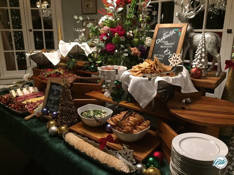 Holiday spread on decorated table. Charcuterie, crostini, tapenade, artichoke spinach dip, brie en croute surrounded by holiday cheer